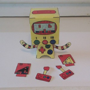 This little dude's name is 8bit! #popbloks #handcrafted #papertoys He comes complete with 2 #game cartridges and dual player #controllers #Robots #8bitvideogames #oldschoolvideogames #tetris #spaceinvaders #art #artwork #watercolorpainting #drawing #creating #building #fun #toys #colorful #handmade #nocomputer #robotsvsmonsters